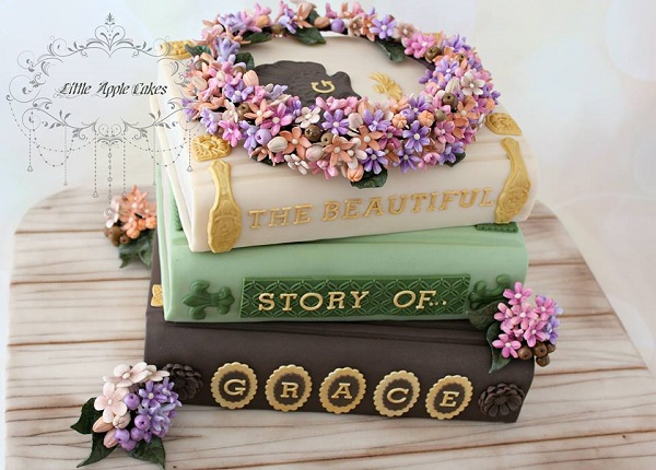 stack of books cake with floral garland cake topper by Little Apple Cakes