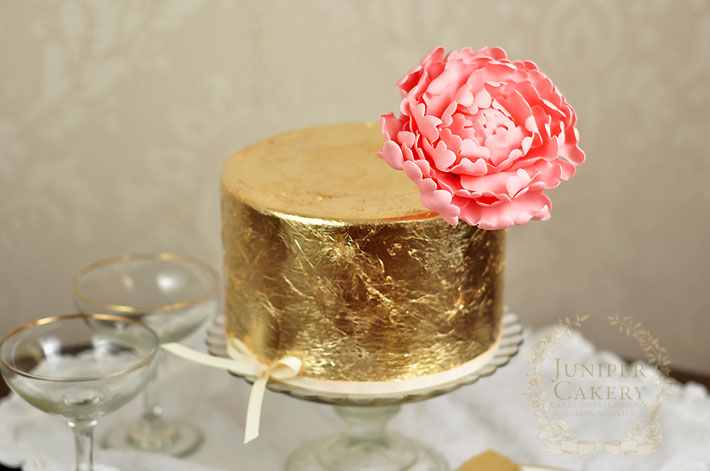 gold leaf covered cake with pink peony by The Juniper Cakery