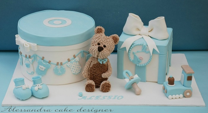 christening cake for a boy with teddy, booties and train by Alessandra Frisoni
