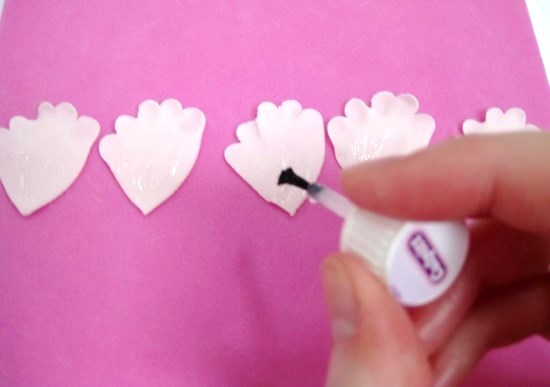 painting edible glue on to gumpaste peony petals