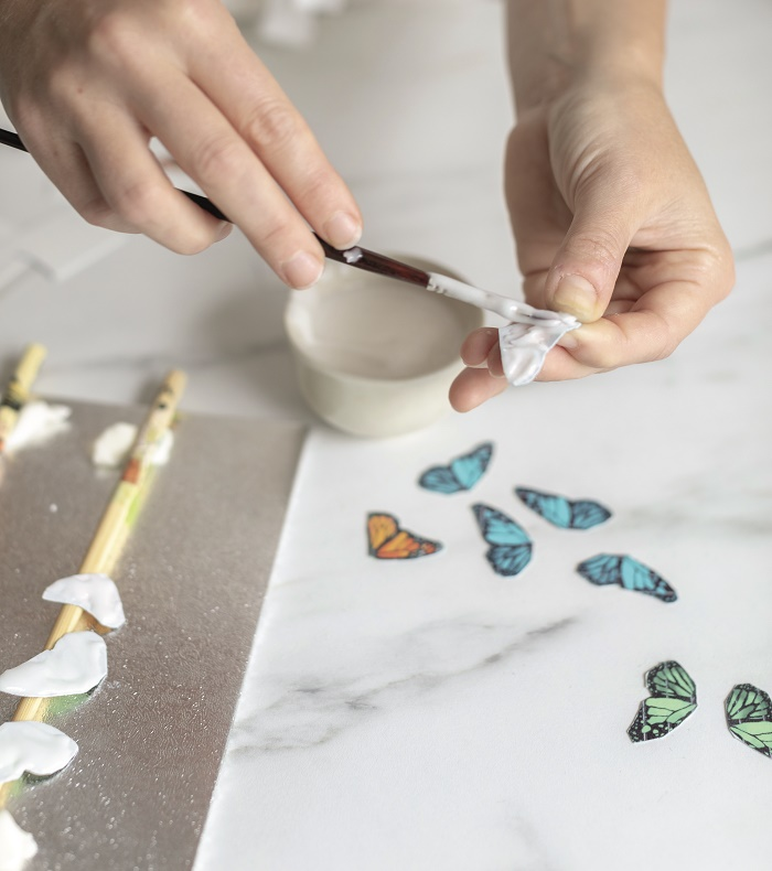 Coating the back of the edible printed butterflies with royal icing to firm them up from Botanical Baking by Juliet Sear