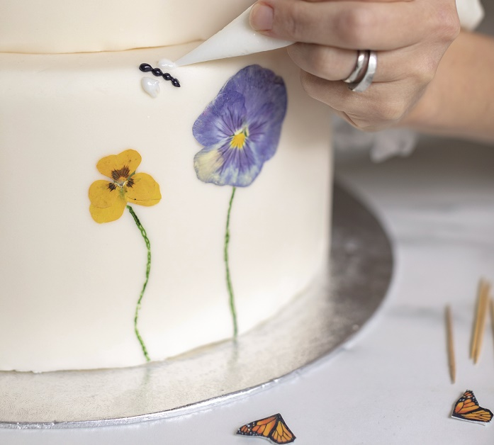 Wildflower Wedding Cake Tutorial, using royal icing to adhere the butterfly wings